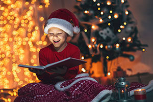 A young boy is reading a children's book on Christmas morning